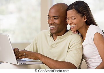 paar, in, woonkamer, gebruikende laptop, en, het glimlachen