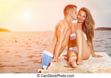 paar, jonge, ondergaande zon , kus, gedurende, strand, vrolijke