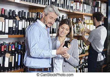 paar, kijken naar, wijn fles, in, winkel