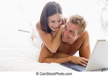 paar, liegen, lächeln, bett, laptop