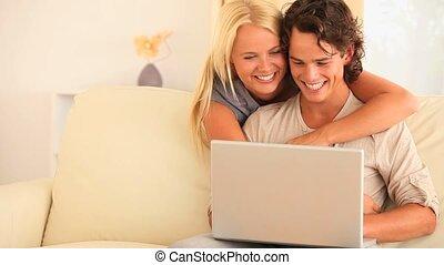 paar, met, een, draagbare computer, op, een, sofa