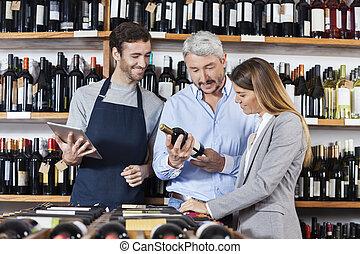 paar, met, wijn fles, staand, door, verkoper, vasthouden, digitale , tabblad