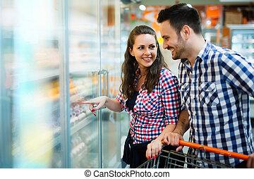 paar, shoppen , in, supermarkt, terwijl, verdragend, boodschappenwagentje