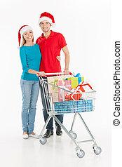 paar, shopping., vrolijk, jong paar, staand, dichtbij, boodschappenwagentje, en, het glimlachen, terwijl, vrijstaand, op wit