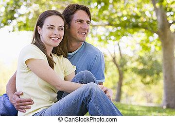 paar, sitzen, draußen, lächeln