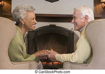 paar, sitzen, in, wohnzimmer, per, kaminofen, halten hände, und, lächeln