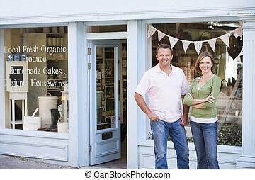 paar, staand, voor, organisch voedsel, winkel, het glimlachen