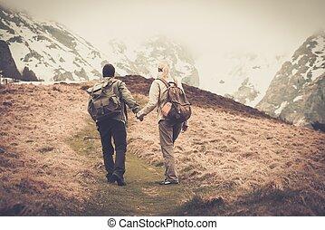 paar, van, hikers, met, rugzakken, wandelende, in de bergen