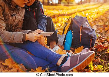 paar, van, toeristen, met, rugzakken, grondig, voor, juiste weg, gebruik, navigator, in, herfst, forest., vrouwen, hebben, rusten
