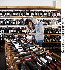 paar, vasthouden, wijn fles, in, supermarkt