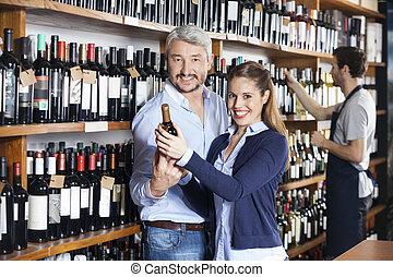 paar, vasthouden, wijn fles, terwijl, verkoper, werkende , in, winkel