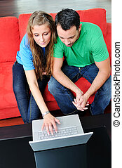 paar, werken, hebben vermaak, thuis, draagbare computer, vrolijke