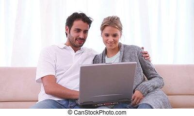 paar, zitten samen, op de bank, terwijl, kijken naar, een, draagbare computer