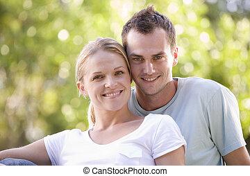 paar, zittende , buitenshuis, het glimlachen