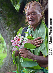 Pacific Islander man looks at exotic flower on eco tourism ...