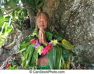 Pacific Islander man praying under a rain forest tree in ...