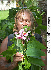 Pacific Islander man smells a flower on eco tourism tour in ...