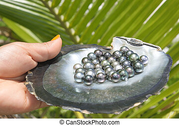 Pacific Islander woman holds Tahitian Black Pearls - Pacific...
