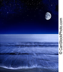 The moon glowing over a calm Pacific ocean shortly after sunset.