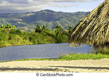 Pacific Ocean estuary with Sierra Madre mountain range in background, Nayarit, Mexico