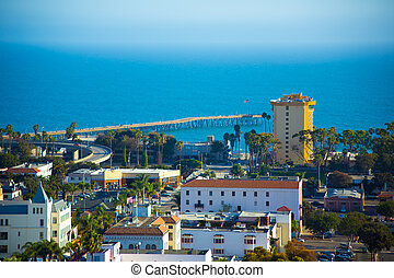 A beautiful view of the Pacific Ocean and the City of Ventura, California. A view of the pier, a high rise hotel, and Spanish style architecture fill the scene.