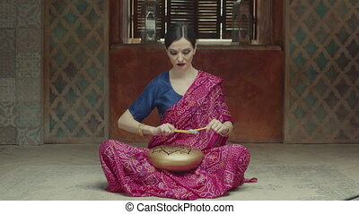 Pacified woman playing glucophone with drums