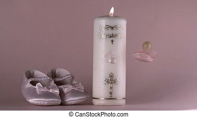 Pacifier falling beside lit baptism candle and baby shoes in...