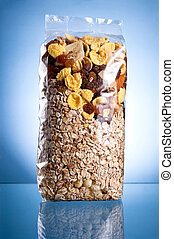 Pack of muesli (Dry breakfast, mixture of corn flakes and dried fruit) on a blue background