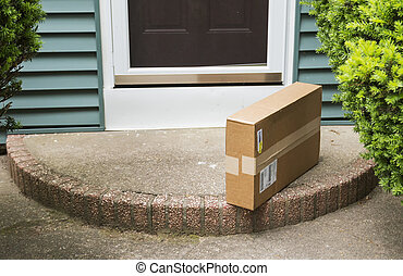 Package left on stoop by front door - A brown cardboard box ...