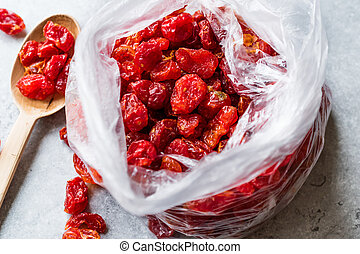 Package of Red Raisins in Plastic Bag with Wooden Spoon.