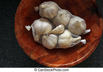 packaged garlic in a wooden bowl