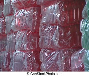 Packaged red and green PET bottles in warehouse.