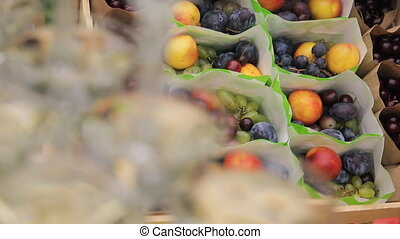 Packages with fresh ripe fruit in box in forest outdoors for holiday