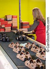 Packaging - Footwear factory worker at the packaging station