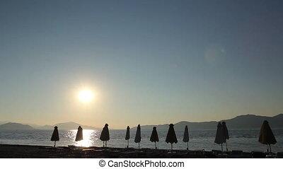 Packed sunshade on the public beach at sundown