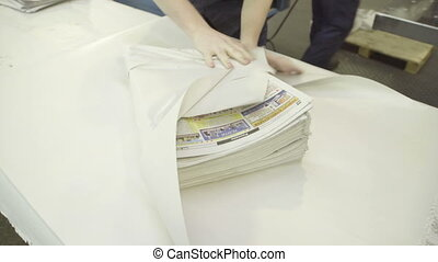 Packer packing newspapers in white wrapping paper in print house