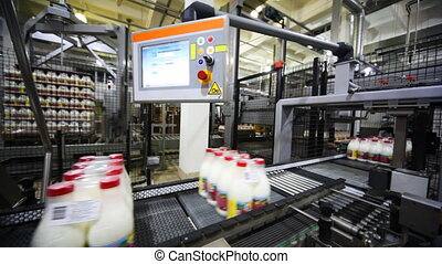 packets to eight bottles of milk move belt conveyors, behind...