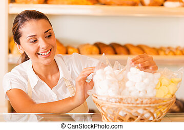 Packing fresh cookies for sale. Beautiful young woman in apron packing cookies and smiling while standing in bakery shop