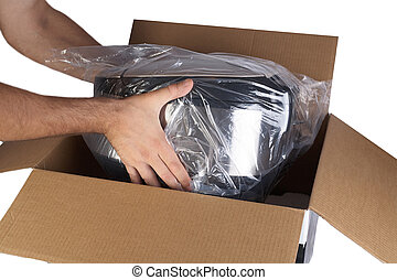 Packing goods in cardboard box with styrofoam material for safe transportation of cargo. Isolated on white background. Man's hands are packing the goods.
