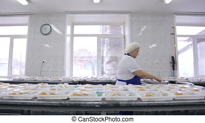 Packing lunch boxes a worker of a catering company. Biggest...