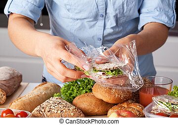 Young woman packing tasty sandwich with lettuce and ham