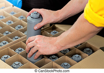 Packing water filters - Worker hands packaging a water...