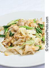 stir fired thin noodles with soy sauce and pork and Kale on white dish
