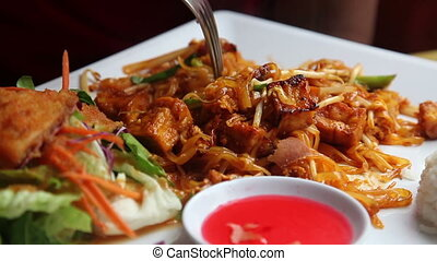 Pad Thai, with someone eating it
