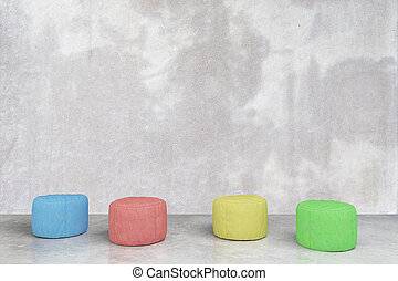 Padded stools in concrete room