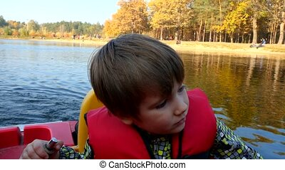 Paddle a canoe. Games on water. Child in canoe. Boy in red ...