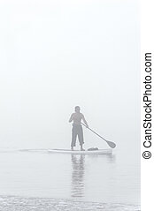 Paddle Board in Early Fog - Young man rowing his paddle...