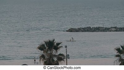 Paddle board sailing along the sea shore - Evening scene of...