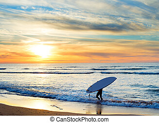 Paddle surfing, Portugal - Man carrying surfboard on the...