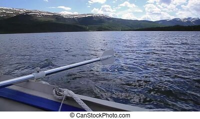 paddle work on the lifeboat on a mountain lake in amazing...